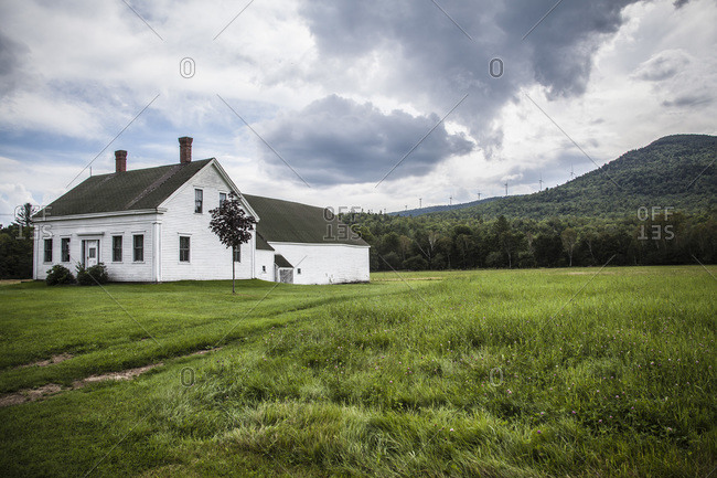 Farmhouse with Wind Turbines on Hill in Background
