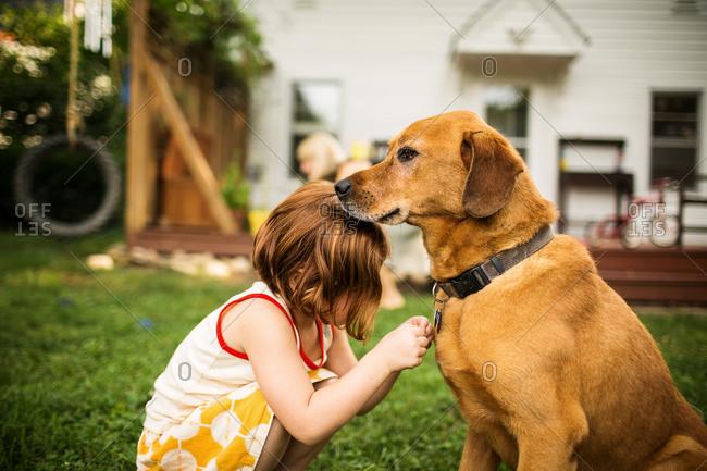 Redhead girl petting dog in garden
