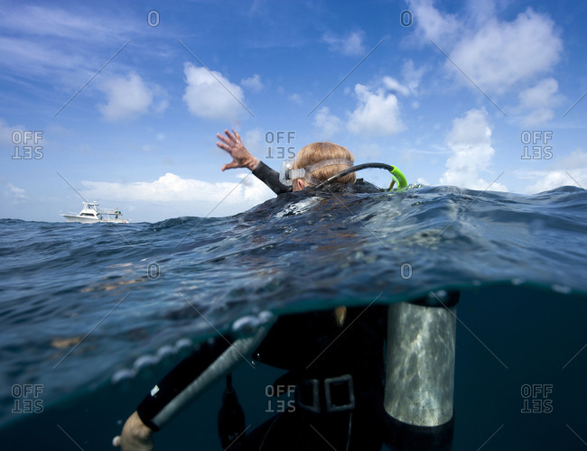 Scuba diver waves to show distress as she requires assistance