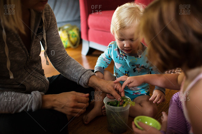 Mother shows children a caterpillar in living room