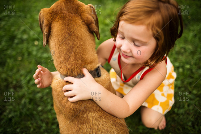Overhead view of redhead girl embraces dog in garden