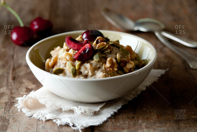 A bowl of fresh oatmeal with pumpkin seeds, walnuts and cherries