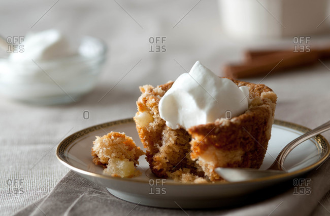 An apple crumb cake with whipped cream