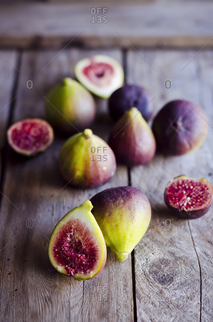 Whole and sliced fresh figs on wooden table
