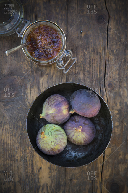 Four figs in a bowl and a glass of fig jam on wooden table