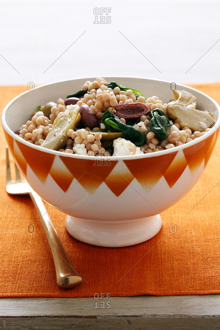 Bowl of Italian pastina with olives, spinach and artichoke