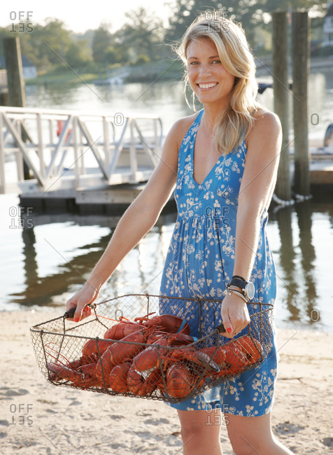 Blond woman holding a basket of lobster