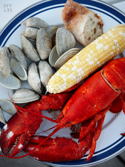 Top view of lobster, clams, cob and rustic bread