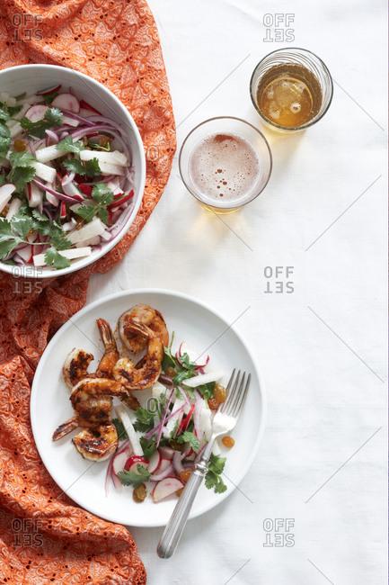 Overhead view of chipotle shrimp with radish and jicama salad