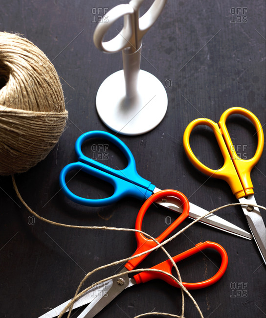 Overhead view of three different color of scissors and twine
