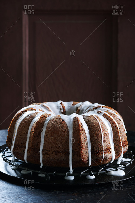 Amaretto and fig cake with frosting on cooling rack