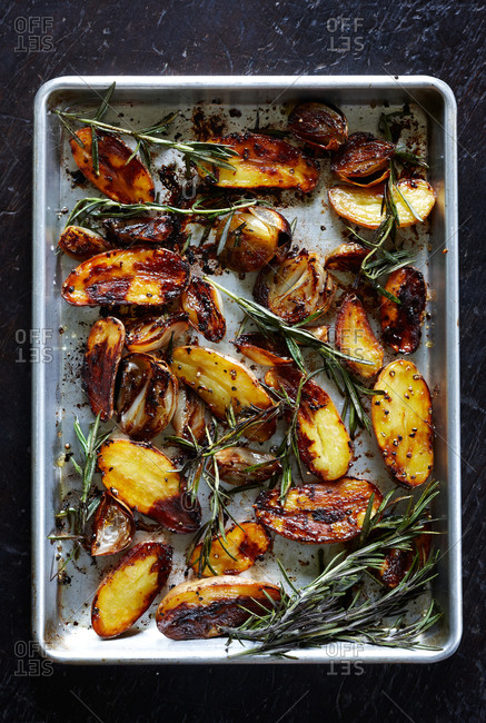 Top view of balsamic baked potatoes with shallots and rosemary