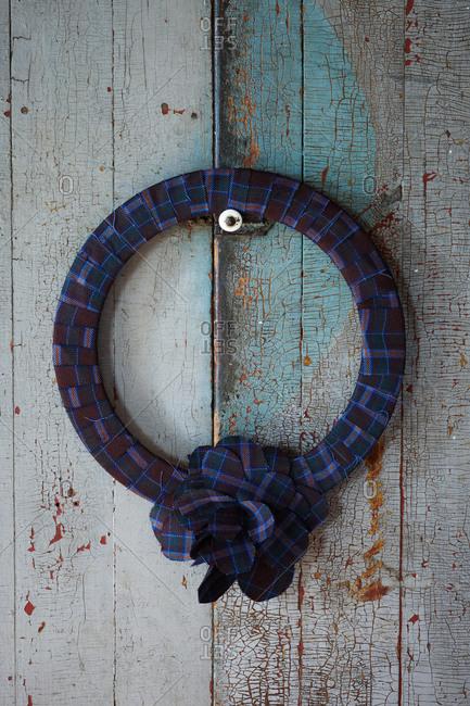 Tartan wreath hanging on rustic door