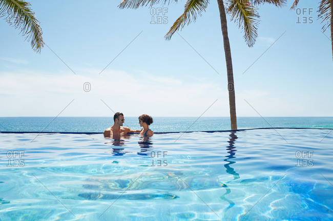 Couple talking in an infinity pool