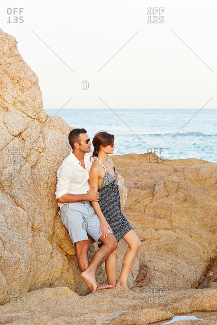 Couple leaning against a rock on the beach