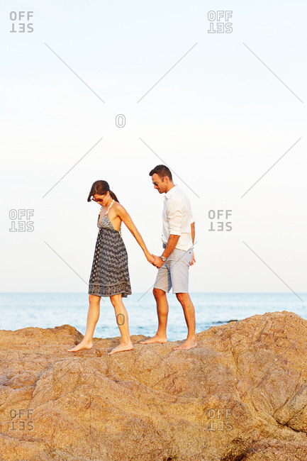 Couple walking on a rock at the beach
