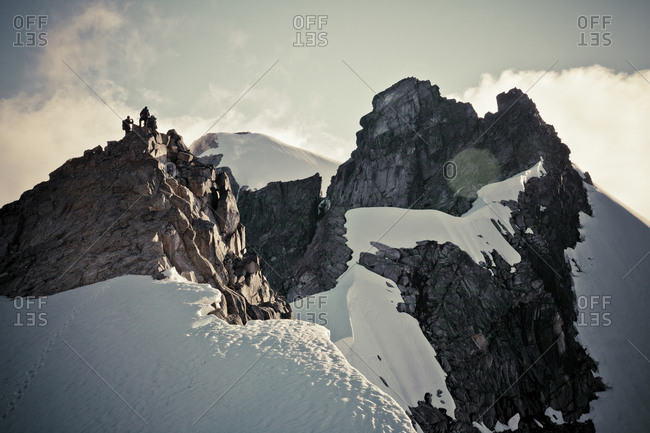 Low angle view of two mountain climber on top of a snowy summit