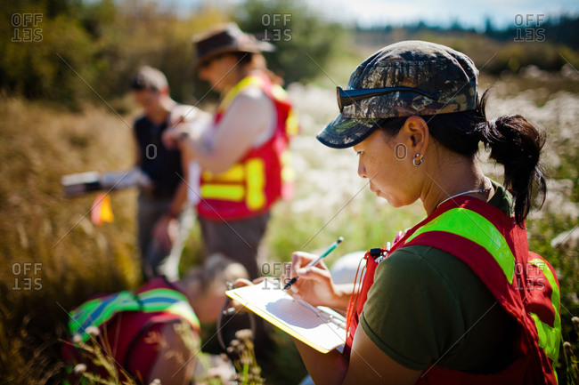 A female researcher taking notes in a field