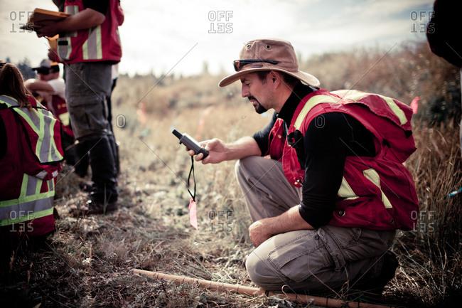Man using a gadget in a field