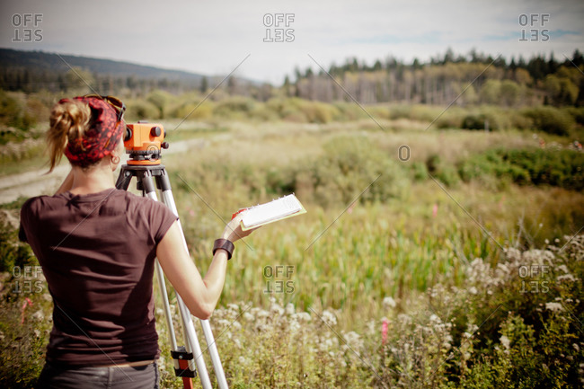 Rear view of a female surveyor with a tripod