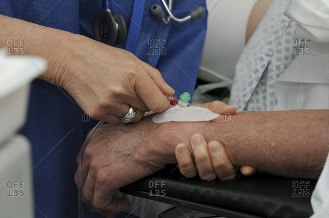 Nurse inserting and IV drip into a patients wrist