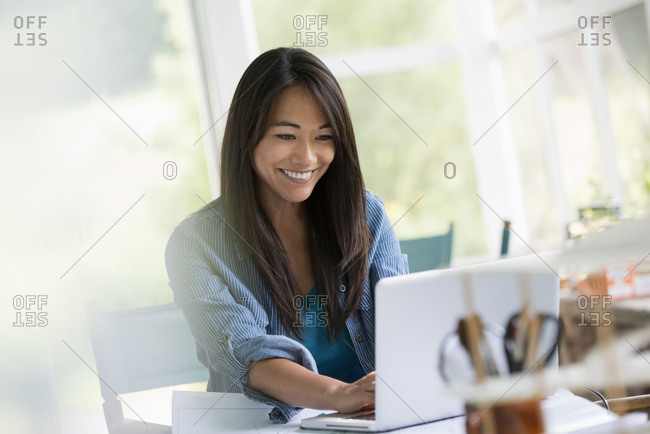 A woman in an office, working at a laptop computer