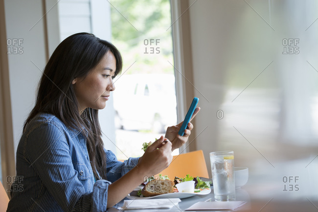 A woman eating a salad and checking her phone