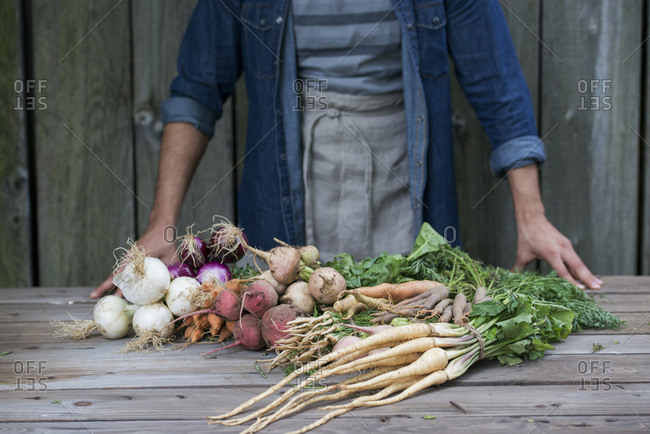 A man sorting freshly picked vegetables on a table