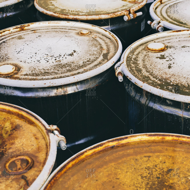 A group of rusted corroded barrels of chemical or petroleum products