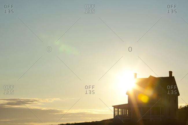 Sun shining behind rural house