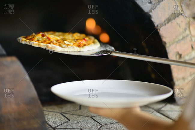 Taking pizza out of a brick oven