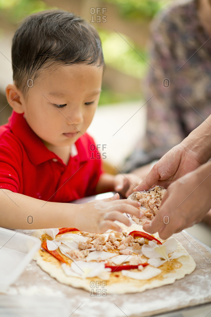 Mother helping son making pizza