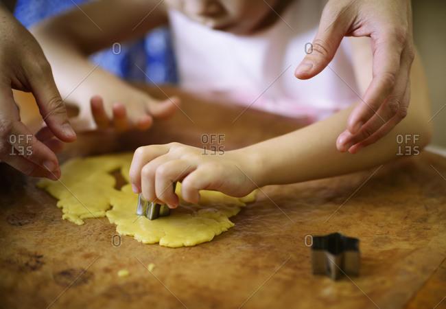 Mom helping daughter cut cookies