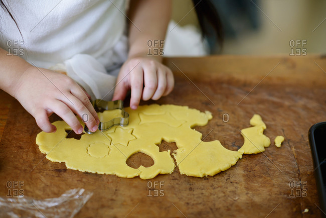 Close up of little girl using cookie cutters