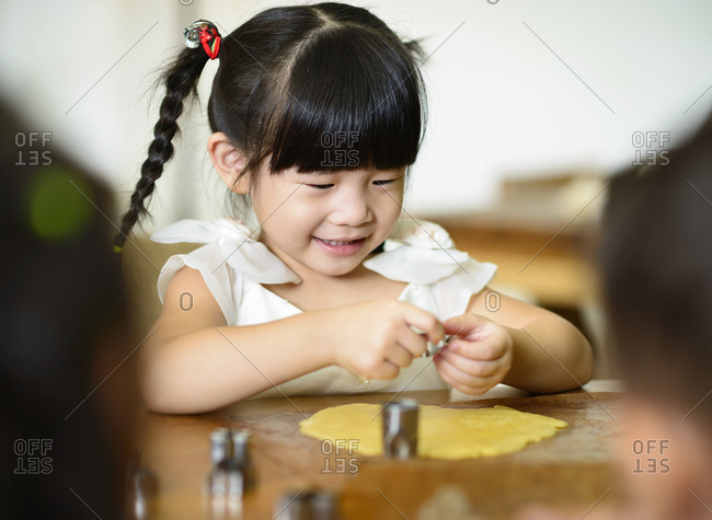 Little girl using cookie cutters