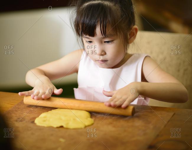 Little girl rolling dough