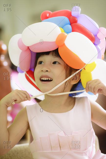 Kid wearing a balloon hat