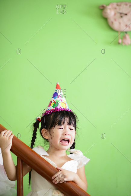 Crying girl wearing a birthday hat