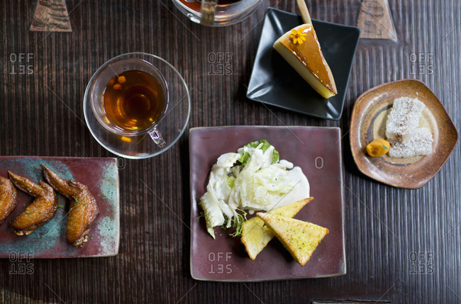 Bread, salad, desserts, cake, tea and grilled chicken wings on wooden table