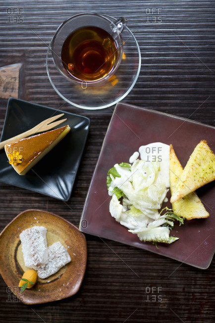 Salad, bread, desserts, cake and tea on wooden table