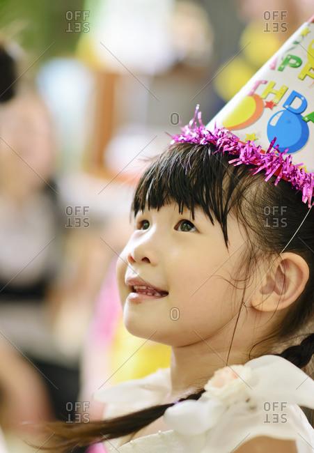 Girl wearing a birthday hat