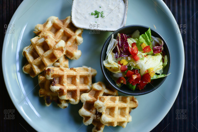Fresh salad and waffles on wooden table