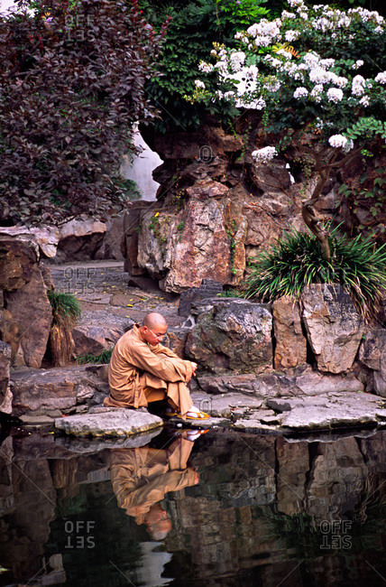 Buddhist monk reflected in Central Pond of Master of Nets Garden