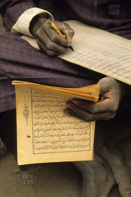 West African Islamic student copying the Koran with pen and ink, Djenne, Mali, West Africa