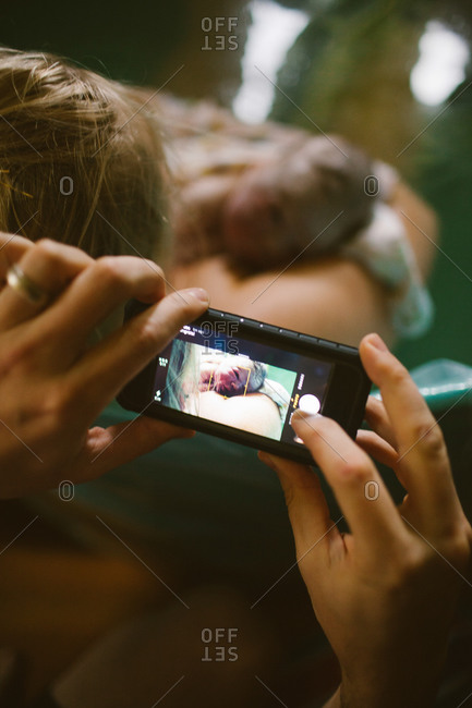 Father taking a picture of his newborn daughter with a smart phone