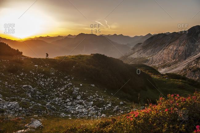 Man hiking through Niedere Tauern mountains at sunrise