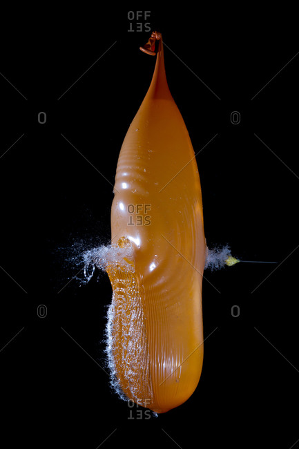 Orange water balloon pricked by needle against black background