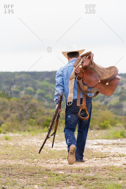 Texan Cowboy walking with rifle and saddle stock photo - OFFSET