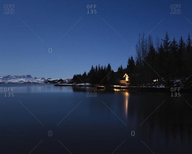 Lit lake house at night