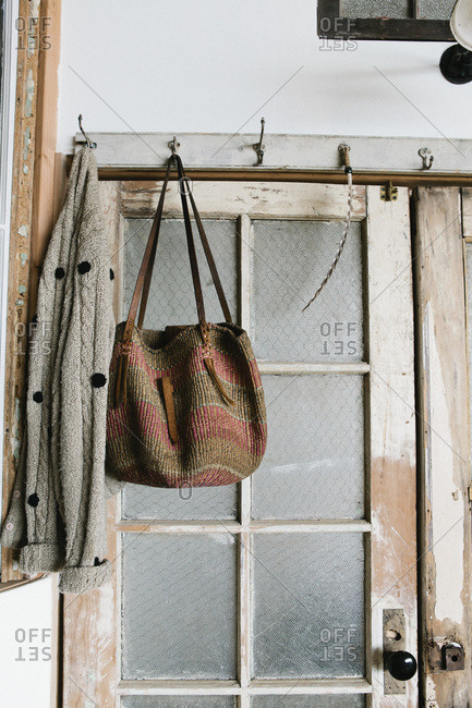 Sweater and a bag hanging by a rustic door